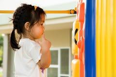 Een klein meisje speelt in speelplaats Stock Foto's