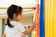 Een klein meisje speelt in speelplaats Stock Foto