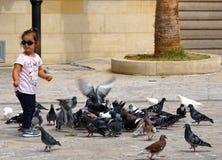Een klein meisje speelt voedende duiven in Heraklion royalty-vrije stock afbeelding