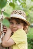 Een klein meisje in een strohoed dichtbij berkboom, zomervakantie stock foto