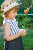 Een klein meisje in een strohoed die groene bladeren, zomervakantie bekijken stock afbeeldingen