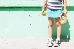 Een klein meisje in tennisschoenen houdt een appel en document zak met een schoolsnack tegen de achtergrond van een groene muur royalty-vrije stock fotografie