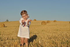 Een klein meisje in traditioneel chemise status blootvoets op een geoogst gebied stock fotografie