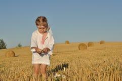 Een klein meisje in traditioneel chemise status blootvoets op een geoogst gebied met oren in haar hand royalty-vrije stock foto