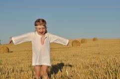 Een klein meisje in traditioneel chemise status blootvoets op een geoogst gebied met oren in haar hand stock afbeelding