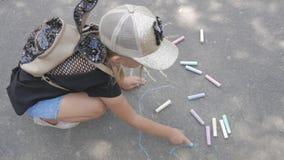 Een klein meisje trekt krijt op het asfalt Het kind trekt de zon in het park stock videobeelden