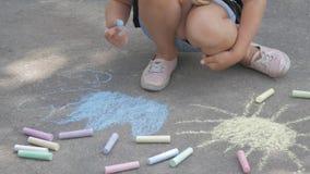 Een klein meisje trekt krijt op het asfalt Het kind trekt de zon in het park stock footage