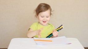 Een klein meisje trekt met kleurpotloden stock videobeelden