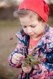 Een klein meisje wihr een boeket van bloemen in haar handen stock afbeeldingen