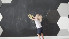 Een klein meisje wist krijt van het bord stock videobeelden