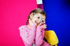 Een klein meisje in witte ronde glazen op een heldere gekleurde achtergrond Royalty-vrije Stock Afbeeldingen