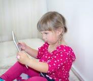 Een klein meisje zit en let op beeldverhalen op een tablet royalty-vrije stock fotografie