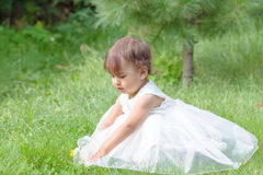Een klein meisje zit op groen gras in een mooie kleding Stock Foto