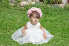 Een klein meisje zit op groen gras in een mooie kleding Stock Fotografie