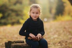 Een klein meisje in zwarte kleren zit op een stomp en speelt met de herfstbladeren Blond haarmeisje royalty-vrije stock foto