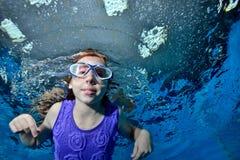 Een klein meisje in zwemmende glazen zwemt onderwater in de pool op een blauwe achtergrond en bekijkt me Portret Sluit omhoog B royalty-vrije stock foto