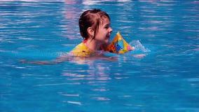 Een klein meisje zwemt in de pool Het kind baadt en bespat in de blauwe pool stock video