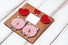 Een klein met de hand gemaakt paneel met een beeld van rode harten van een paar van varkens en een kleine prentbriefkaar op witte royalty-vrije stock foto