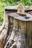Een klein model van een huis op een stomp Stock Foto's