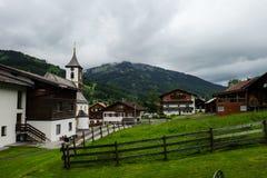 Een klein Oostenrijks dorp met typische huizen en een kerk stock foto
