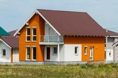 Een klein oranje huis met witte vensters en een donker bruin metaaldak royalty-vrije stock foto's