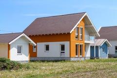 Een klein oranje huis met witte vensters en een donker bruin metaaldak royalty-vrije stock fotografie