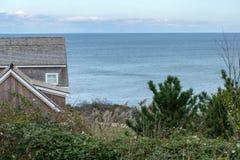 Een klein plattelandshuisje, groene struiken en struiken, tegen de blauwe horizon op de achtergrond, Blokeiland, RI, de V.S. stock foto