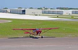 Een klein rood propellervliegtuig Stock Fotografie