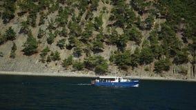 Een klein schip in overzees tegen een rotsachtig voorgebergte Op een zonnige de zomerdag stock videobeelden