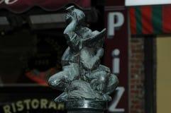 Een klein standbeeld van twee mensen het drinken Stock Foto