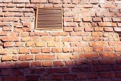 Een klein venster met een rooster op een oude bakstenen muur stock foto's