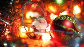 Een klein zilveren cijfer van Santa Claus bevindt zich dichtbij een rode Kerstmis Hangende Snuisterij op de lijst Het knipoogje v stock videobeelden