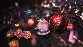 Een klein zilveren cijfer van Santa Claus bevindt zich dichtbij een rode Kerstmis Hangende Snuisterij op de lijst Het knipoogje v stock video