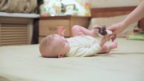 Een kleine baby ligt op een groot bed, mammaspelen met een baby stock videobeelden