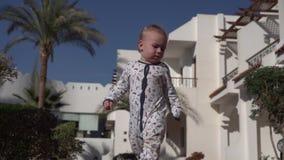 Een kleine baby loopt onhandig langs een weg op een tropisch gebied in langzame motie stock videobeelden