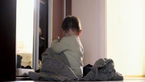 Een kleine baby van de meisjespeuter thuis dichtbij de spiegel die, onafhankelijk montessorispel zich omhoog kleden stock videobeelden