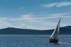 Een kleine boot die in het overzees met mooie hemel op de achtergrond varen stock foto