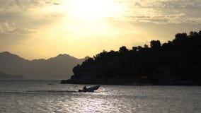 Een kleine boot vaart in een mooie baai tijdens zonsondergang in langzame motie stock footage