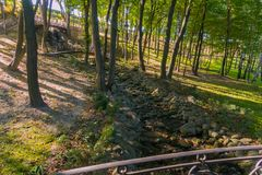 Een kleine bosbron onder de ronde en ovale stenen tussen de bomen Stock Afbeeldingen