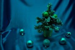 Een kleine die Kerstboom in een pot, met ballen, slingers en lichten wordt verfraaid Royalty-vrije Stock Fotografie