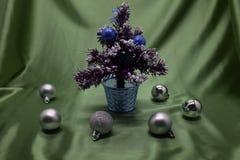 Een kleine die Kerstboom in een pot, met ballen, slingers en lichten wordt verfraaid Royalty-vrije Stock Foto