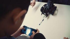 Een kleine geïnteresseerde jongen controleert de robot met een klauw op vier wielen met een in hand telefoon stock footage