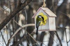 Een kleine gele mees zit op een geel vogel en eekhoornvoederhuis van triplex in het park stock fotografie