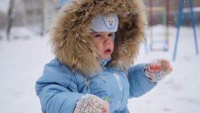Een kleine gelukkige kindspelen met sneeuwvlokken in het park stock footage
