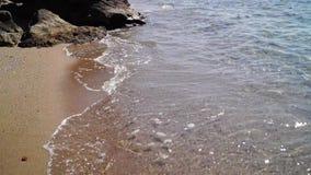 Een kleine golf op het strand, Golf van Santorini-eiland stock video