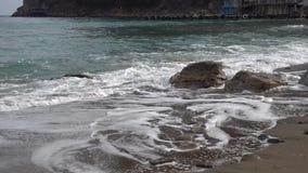Een kleine golf van de zuivere looppas van de Zwarte Zee op een steen op het verlaten zandige strand van het dorp van Novy Svet i stock footage