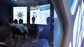 Een kleine groep mensen van Aziatische nationaliteit bekijkt het grote scherm in de zaal tijdens de conferentie stock videobeelden