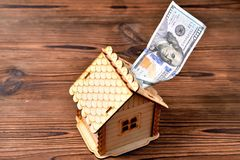 Een kleine houten huis-piggy bank en een geldrekening van 100 dollars Royalty-vrije Stock Foto