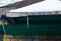 Een kleine ijskegel op een groen dak onder de sneeuw stock fotografie