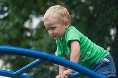 Een kleine jongen beklimt en hangt op een metaalladder royalty-vrije stock fotografie